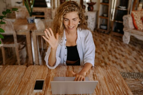Woman sitting at table on video call through an apple computer. Her hand is raised and waving hello at the screen.